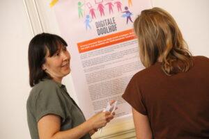 Deelnemers in gesprek bij poster praktijk case 'Digitale Doolhof'
