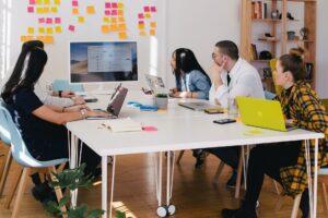 mensen met laptop achter tafel kijkend naar scherm en post-its